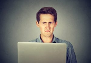 frustrated-man-looks-at-laptop